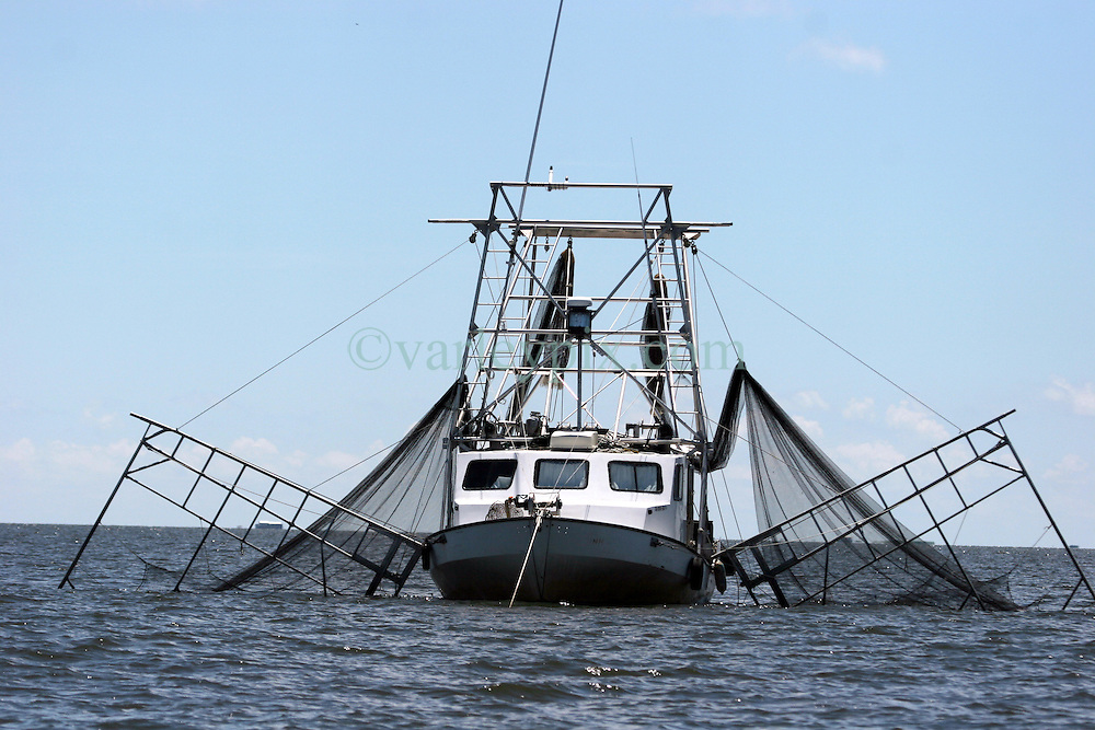 21 August 2010. Barataria Bay, south Louisiana. <br /> A shrimp boat sits in the current deploying nets instead of oil boom in the water, <br /> Photo credit; Charlie Varley/varleypix.com