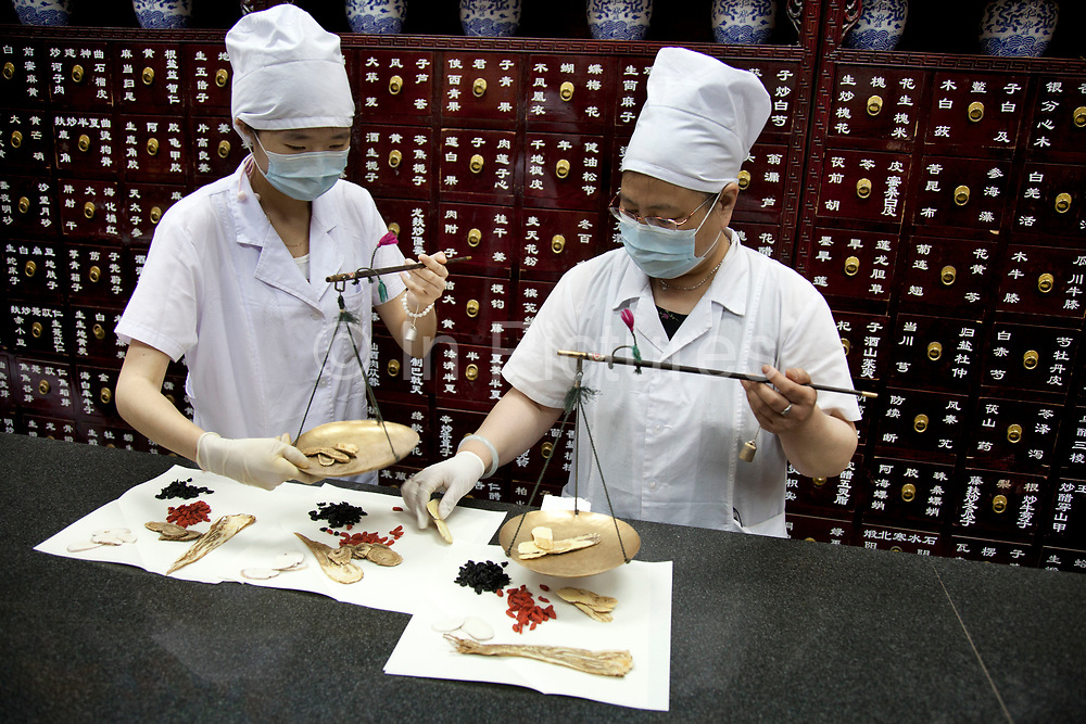 The preparation of traditional Chinese medicine at the Beijing Tongrentang drug store, which was established in 1669 during the Qing Dynasty and holds a high reputation in China. Chemists weigh out and wrap up various herbal elements including berries, roots, bark and shavings. Traditional Chinese Medicine refers to a broad range of practices sharing common theoretical concepts which have been developed in China and are based on a tradition of more than 2,000 years, including various forms of herbal medicine and dietary therapy. Although these practices are considered alternative medicine in the Western world, they are a common part of medical care throughout East Asia, accounting for estimated 40% of all health care delivered in China.