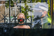 A Police wearing face mask walk by a Topless Climate activist who locked themselves against the railings of the Houses of Parliament, during an Extinction Rebellion (XR) protest, in London on Thursday, Sept. 10, 2020. Environmental nonviolent activists group Extinction Rebellion enters its 10th and final day of continuous ten days protests to disrupt political institutions throughout peaceful actions swarming central London into a standoff, demanding that central government obeys and delivers Climate Emergency bill. (VXP Photo/ Vudi Xhymshiti)