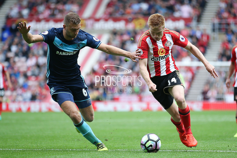 Sunderland forward Duncan Watmore (14)  takes on Middlesbrough defender Ben Gibson (6)  during the Premier League match between Sunderland and Middlesbrough at the Stadium Of Light, Sunderland, England on 21 August 2016. Photo by Simon Davies.