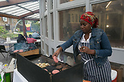 A lady BBQs beef burgers during a TRA, Tenants and residents association, community day at the Cressingham Gardens rotunda on 9th September 2015 in South London, United Kingdom. Cressingham Gardens is a council garden estate, located on the southern edge of Brockwell Park. It comprises of 306 dwellings and built to the design of Lambeth Borough Council architect Edward Hollamby in the early 1970s. In 2012, Lambeth Council proposed regeneration of the estate, a decision highly opposed by many residents. Since the announcement, the highly motivated campaign group Save Cressingham Gardens has been active.