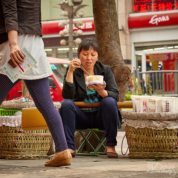 A street vendor stops for lunch in downtown Chongqing as busy people pass by.
