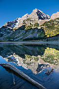 The Maroon Bells reflect in Crater Lake. The Maroon Bells are two adjacent peaks of the Elk Mountains: Maroon Peak 14,163 feet on left, seen behind North Maroon Peak 14,019 feet, in Maroon Bells-Snowmass Wilderness of White River National Forest. The mountains are on the border between Pitkin County and Gunnison County, 12 miles southwest of Aspen, in Colorado, USA.