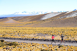 "© Licensed to London News Pictures. 06/06/2013. Chile, UK. Runners run a test event on the route of the inaugural ""Volcano Marathon"". The inaugural UVU Volcano Marathon takes place on 14th November 2013. Competitors will assemble at San Pedro de Atacama in the heart of the Atacama Desert, the driest desert in the world. The race will begin at the Tropic of Capricorn adjacent to Lascar Volcano, one of the most active volcanoes in Northern Chile. Despite the desert setting, there is a strong likelihood of snow on the ground at the start line. At an altitude of 4,300 metres (14,100 feet), the impact of thinner air will also be felt by competitors.. Photo credit : Mike King/LNP<br />