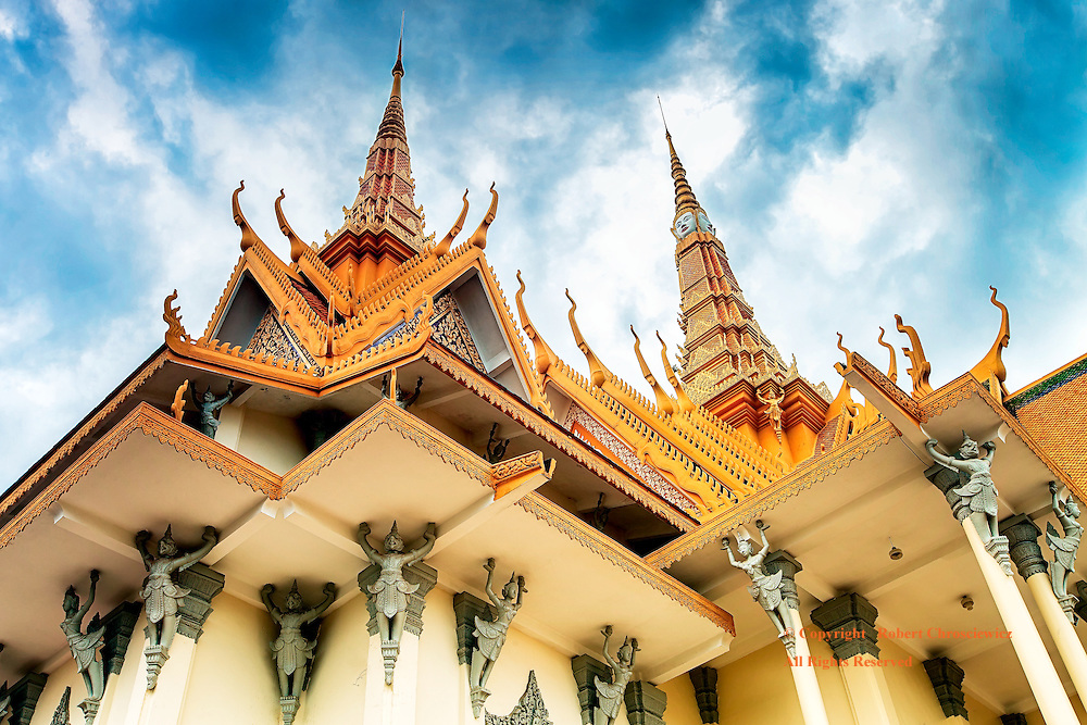 Spires to the Sky: A wide angle view, looking up at the Throne Hall, reveals multiple stories held up by grey-green Garuda statues and culminates with two golden spires, Imperial Palace, Phnom Penh Cambodia.