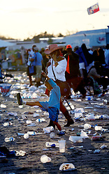 05 May 2013. New Orleans, Louisiana,  USA. .New Orleans Jazz and Heritage Festival. JazzFest..A kicks and dances his way through trash at the end of the festival. .Photo; Charlie Varley