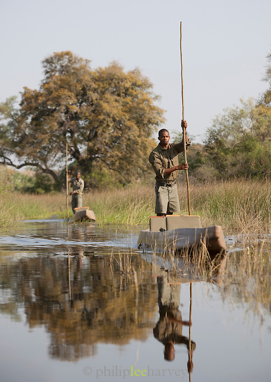 Local guides from Abu Camp, a luxury safari camp, travel through the Okavango Delta by makoro, a dug out canoe in Botswana