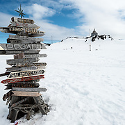 Signposts in Russian point to world destinations and their distance from Bellingshausen Station research base on King George Island in the South Shetland Islands. In the background at right is Trinity Church.