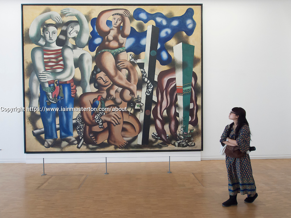 Woman looking at painting Composition aux deau Perroquets by Fernand Leger at Pompidou center  modern  art museum in Paris France