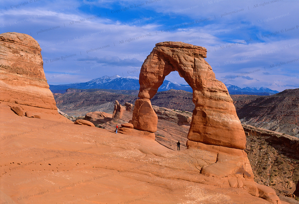 Hikers stand below Delicate Arch, the symbol of Utah in Arches National Park, near Moab.  Their are over 2000 natural sandstone arches in the park, from just over 3 ft. to over 89 meters.