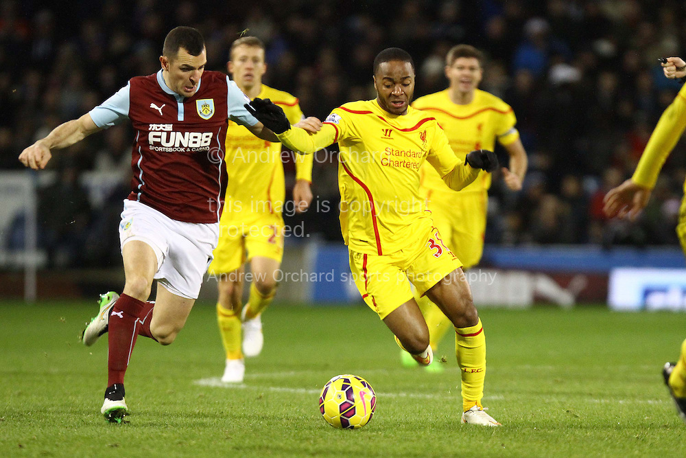 Dean Marney of Burnley looks to tackle Raheem Sterling of Liverpool. Barclays Premier league match, Burnley v Liverpool at Turf Moor in Burnley, Lancs on Boxing Day, Friday 26th December 2014.<br /> pic by Chris Stading, Andrew Orchard sports photography.