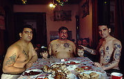 Roma Gypsies-beyond borders. David, his brother and brother-in-law. His family celebrate Orthodox Catholic Christmas. The  family is half Muslim, so chicken is served together with the traditional fattened pig. In traditional Roma style, the  women serve, but do not eat at the table with the men. Belgrade, Serbia.  January 7th 2004.<br /><br />Orthodox Christmas Belgrade. serbia. Midday 7th January.<br />Dzavid Berisa (Driver)39yrs with Gazmen (Painter) brother of Dzavid, LHS and his brother in law Mile.<br /><br />Elvira LHS Gazmen's daughter and Miroslav Dzavid's granddaughter RHS<br /><br />Food-Pig meat. Sarma - cabbage wrapped sausage meat rolls. Cesnica - a christmas bread with a piece of money inside - the one who finds it will have a prosperous year. Salad, chicken noodle soup. Fruit and nuts and tangerines, dried figs and prunes all traditional. Biscuits - wafers with chocolate.