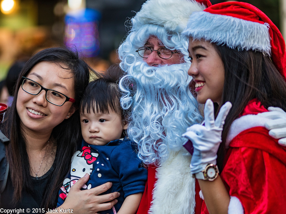 25 DECEMBER 2015 - SINGAPORE, SINGAPORE:  A man in a Santa Claus suit poses for photos with shoppers on Orchard Road in Singapore. Orchard Road is the heart of Singapore's upscale shopping and consumerism.    PHOTO BY JACK KURTZ