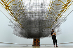 "© Licensed to London News Pictures. 16/09/2019. LONDON, UK. A staff member poses next to """"Matrix III"", 2019, by Antony Gormley. Preview of a new exhibition by Antony Gormley at the Royal Academy of Arts.  The show bring together existing and specially conceived new works from drawing to sculptures to experimental environments to be displayed in all 13 rooms of the RA's Main Galleries 21 September to 3 December 2019.  Photo credit: Stephen Chung/LNP"