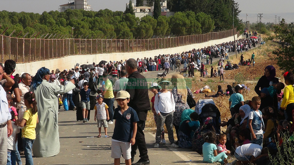 August 21, 2017 - Kilis, Turkey- Thousands of Syrian refugees that have been living in Turkey are going to their country for a Kurban Bayram Fest visit. Syrians are passing the Turkish-Syrian border from Cilvegozu Border Gate near Hatay region of Turkey. Last year, 35.000 Syrians of 120.000 came back to Turkey after Ramadan Bayram Fest. (Credit Image: © Depo Photos via ZUMA Wire)