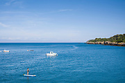 Holidaymaker paddle-boarding and moored pleasure craft in Rozel in St Martin region of Jersey, Channel Isles