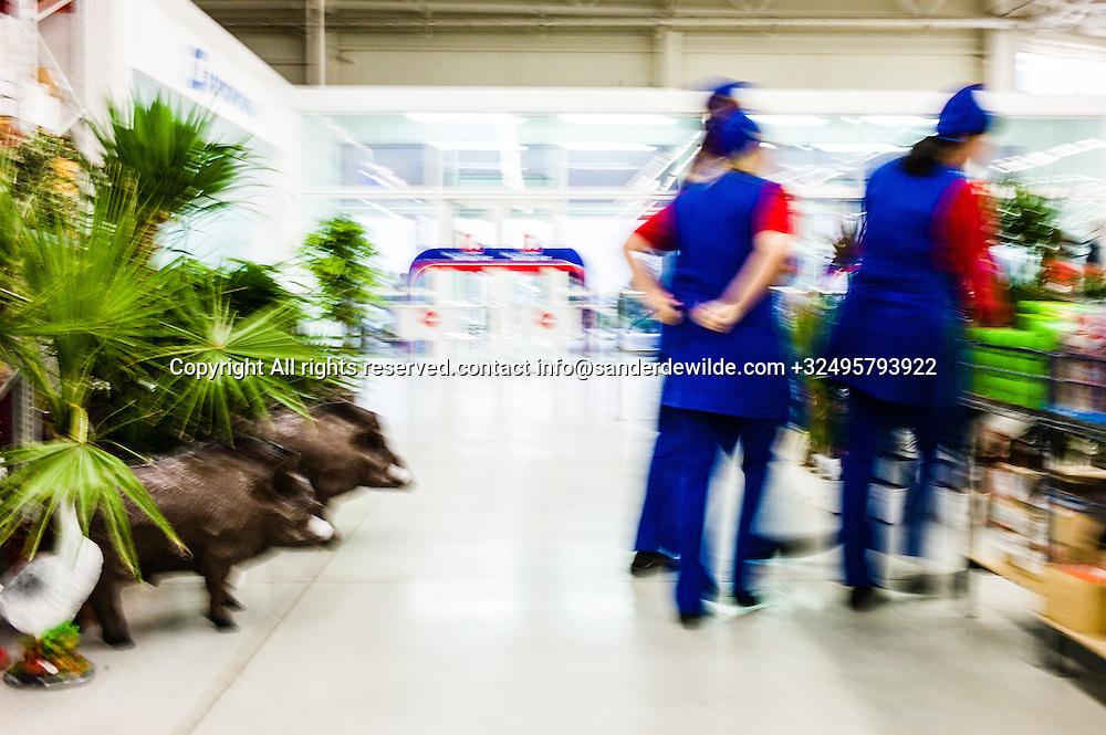 20150826 Tiraspol,  Moldova, Transnistria girls in uniform walk by plastic wild pics in the hypermarket of Sheriff in Tiraspol