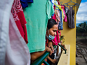 24 JANUARY 2018 - LIGAO, ALBAY, PHILIPPINES: LANIE TAGALO, an evacuee from a community near the Mayon volcano, looks out from the laundry hanging in the school she is temporarily living in in Ligao with 1,849 other people from the volcano. The Mayon volcano continued to erupt Tuesday night and Wednesday forcing the Albay provincial government to order more evacuations. By Wednesday evening (Philippine time) more than 60,000 people had been evacuated from communities around the volcano to shelters outside of the 8 kilometer danger zone. Additionally, ash falls continued to disrupt life beyond the danger zones. Several airports in the region, including the airport in Legazpi, the busiest airport in the region, are closed indefinitely because of the amount of ash the volcano has thrown into the air.    PHOTO BY JACK KURTZ