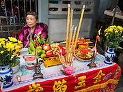 """23 JUNE 2015 - MAHACHAI, SAMUT SAKHON, THAILAND:  A woman sits at the altar she built for the City Pillar Shrine while she waits for the procession to pass her in Mahachai. The Chaopho Lak Mueang Procession (City Pillar Shrine Procession) is a religious festival that takes place in June in front of city hall in Mahachai. The """"Chaopho Lak Mueang"""" is  placed on a fishing boat and taken across the Tha Chin River from Talat Maha Chai to Tha Chalom in the area of Wat Suwannaram and then paraded through the community before returning to the temple in Mahachai.  PHOTO BY JACK KURTZ"""