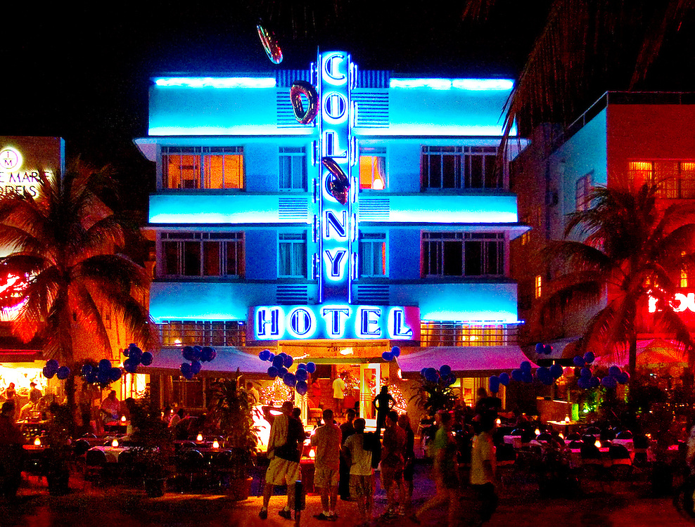 South Beach's Ocean Drive at night with neon, balloons and people. The landmark Art Deco-style Colony Hotel was designed by Henry Hohauser in 1935.