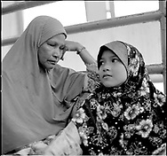 A young girl sits beside her blind mother at a market in Borneo, Malaysia, Southeast Asia