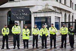 London, UK. 13 October, 2019. Metropolitan Police officers observe a protest by disabled climate activists from Extinction Rebellion outside New Scotland Yard.