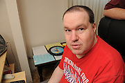 A middle aged autistic man lost his job of many years doing data entry with a local police department after the non-profit organization that paid for his job coach ceased to fund the position.  He now spends time at home on the computer.