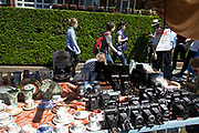 Vintage cameras for sale on a stall on Portobello Road Market in Notting Hill, West London, England, United Kingdom. People enjoying a sunny day out hanging out at the famous Sunday market, when the antique stalls line the street.  Portobello Market is the worlds largest antiques market with over 1,000 dealers selling every kind of antique and collectible. Visitors flock from all over the world to walk along one of Londons best loved streets.