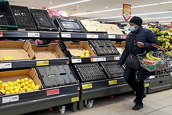 © Licensed to London News Pictures. 06/01/2021. London, UK. A shopper wearing a protective face covering walks past empty crates in Sainsbury's supermarket in north London as the store runs low on fruit and vegetables, following the national lockdown. Prime Minister Boris Johnson announced on Monday 4 January 2021 that England will go into third national lockdown after the mutated variant of the SARS-Cov-2 virus continues to spread around the country, and asked everyone to 'stay at home' and only leave for the specific reasons, until mid-February. <br /> Photo credit: Dinendra Haria/LNP
