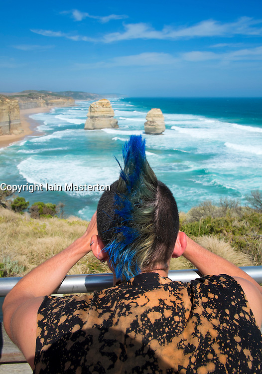 Punk man looking at famous Twelve Apostles landforms on coast of Victoria in Australia