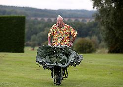 © Licensed to London News Pictures. 14/09/2018. HARROGATE, UK.  Ian Neale of Newport poses for photographs with his winning Giant cabbage of 30.2kg. Harrogate Autumn Flower Show runs from 14-15 September with over 5,000 blooms and an expected attendace of 60,000 visitors at the Yorkshire Showground in Harrogate..  Photo credit: Nigel Roddis/LNP