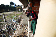 One of the residents washes his teeth on the balcony of the building.