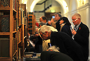 ©London News pictures...04/11/2010. Booklovers browse the Chelsea Antiquarian Book Fair. The 20th annual Chelsea Antiquarian Book Fair takes place at Old Chelsea Town Hall in London. The fair is administered by the Antiquarian Booksellers' Association and features over 75 top dealers from across the United Kingdom. They are brought together under one roof to sell a huge variety of material - rare books, prints, atlases, maps, photographs, ephemera, letters and manuscripts - ranging in price from just a few pounds to many thousands.