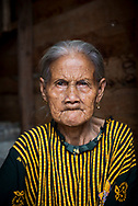 Palangkaraya, Indonesia - March 10, 2017: An old woman sits in the entrance to a home in the waterfront neighborhood on the Kahayan River in Palangkaraya, Central Kalimantan, Indonesia.
