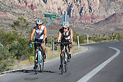 Twee vrouwelijke wielrenners rijdt over de fietsstrook langs de Red Rock Canyon Road buiten Las Vegas. De weg is populair bij fietsers.<br /> <br /> Two female cyclists ride their road bikes near Red Rock Canyon Road outside of Las Vegas. The route is popular by cyclists.