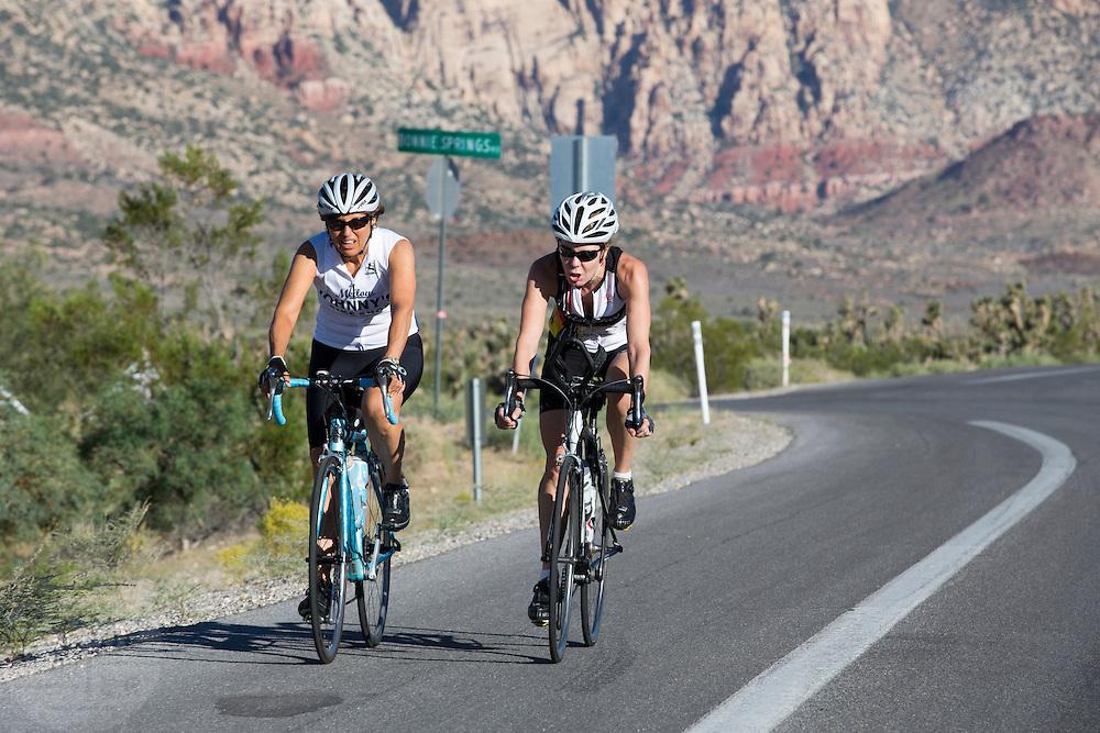 Twee vrouwelijke wielrenners rijdt over de fietsstrook langs de Red Rock Canyon Road buiten Las Vegas. De weg is populair bij fietsers.<br /> <br /> Two female cyclists ride their road bikes near Red Rock Canyon Road outside of Las Vegas. The route is popular by cyclists.
