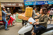 05 APRIL 2012 - HANOI, VIETNAM:   People load up a motorcycle in a market in Hanoi, the capital of Vietnam. Motorcycles are the main means of transportation for millions of VIetnamese who use them for everything from personal transport to delivery vehicles.   PHOTO BY JACK KURTZ