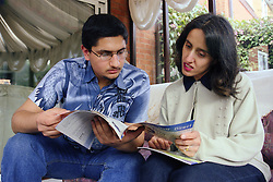 Single mother and teenage son sitting on sofa reading information brochure,