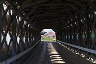 A barn viewed through the Prud'homme covered bridge on Chemin du Pont Prud'homme.  The covered bridge spans the Rivière du Diable (Devils River) near the Village of Brébeuf, Quebec, Canada.  The Prud'homme covered bridge was built in 1918, 100 years before this photograph was made.