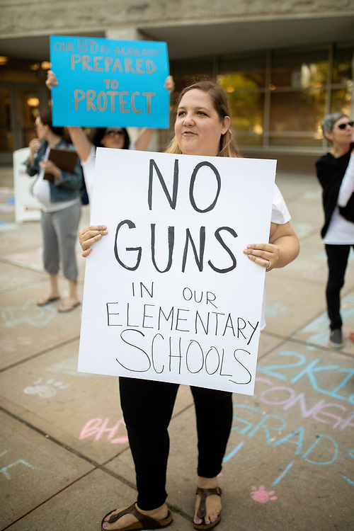 Danielle Kepler joins other Bloomfield residents and parents of school children as they protest a plan by the Bloomfield Board of Education to hire armed officers for each elementary school. Beeks, a teacher in Brooklyn, recently moved to Bloomfield and her son will be a first grade student in the fall. <br /> 6/5/18 Photo by John O'Boyle
