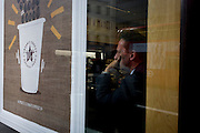 A serious businessman looks pensive through the window of a Pret a Manger in the City of London.