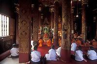 Luang Prabang, Laos, a UNESCO World Heritage Center..prayer in a temple