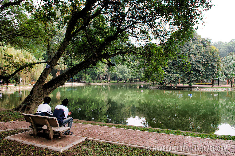 Two young men sit on a bench overlooking a small lake at the Hanoi Botanical Gardens (Vuon Bach Thao).