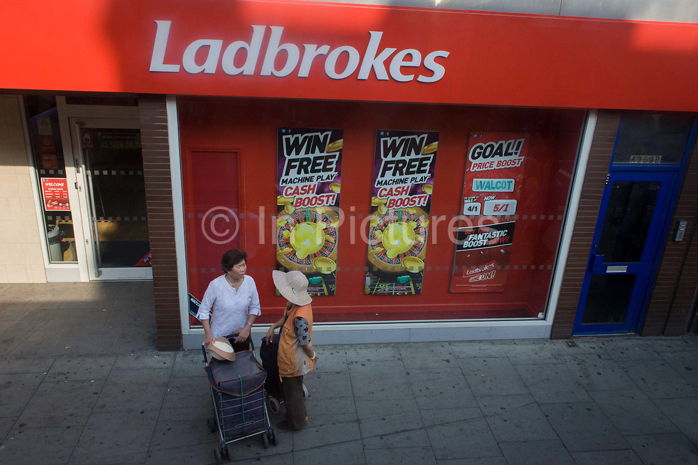Two women of Asian origin stand chatting outside a branch of the betting business, Ladbrokes in south London. Seen from a high perspective - from the top deck of a London bus - we look down on the people as they stop to talk outside of this betting outlet. Posters on the wall advertise the latest deals for playing machine games for prizes, hoping to lure the addictive into spending more on gambling. Ladbrokes plc is a British based gaming company founded by Messrs Schwind and Pendleton in 1886 as commission agents for horses trained at Ladbroke Hall in Worcestershire. The name Ladbrokes was adopted in 1902 when one Arthur Bendir joined the partnership and operations were moved to London. It is today listed on the London Stock Exchange and is a member of the FTSE 250 Index, having been relegated from the FTSE 100 Index in June 2006.