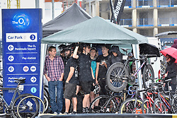 © Licensed to London News Pictures. 22/07/2017. London, UK. World class cyclists take shelter ahead of the London stage of the Red Hook Criterium around Greenwich Peninsula.  Heavy rain showers made riding laps around the 1km street circuit on fixed gear bicycles with no brakes even more of a challenge as riders negotiated multiple heats to try to qualify for an evening final. Photo credit : Stephen Chung/LNP