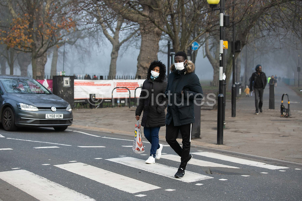 A couple wearing white face masks cross a pedestrian crossing on 6th of December 2020 in Hackney, London, United Kingdom. The national lockdown 2 in England has just ended and the city is now in tier 2. Wearing a face mask is mandatory when social distancing is not possible and many wear their masks outdoors in public.