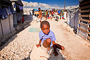 18 NOVEMBER 2010 - PORT-AU-PRINCE, HAITI:  A child sits on a rock near a water distribution site in a tent city in Cite Soliel in Port-au-Prince. Cite Soleil, a sprawling slum area in PAP is ground zero for the cholera epidemic in the Haitian capital. An outbreak of cholera in northern Haiti about a month ago has spread across the nation. Tens of thousands of people have been hospitalized and treated for cholera and more than 1,100 have died. Cholera is a water borne illness that causes severe diarrhea and death by dehydration in a matter of hours.      PHOTO BY JACK KURTZ  choleraepidemic