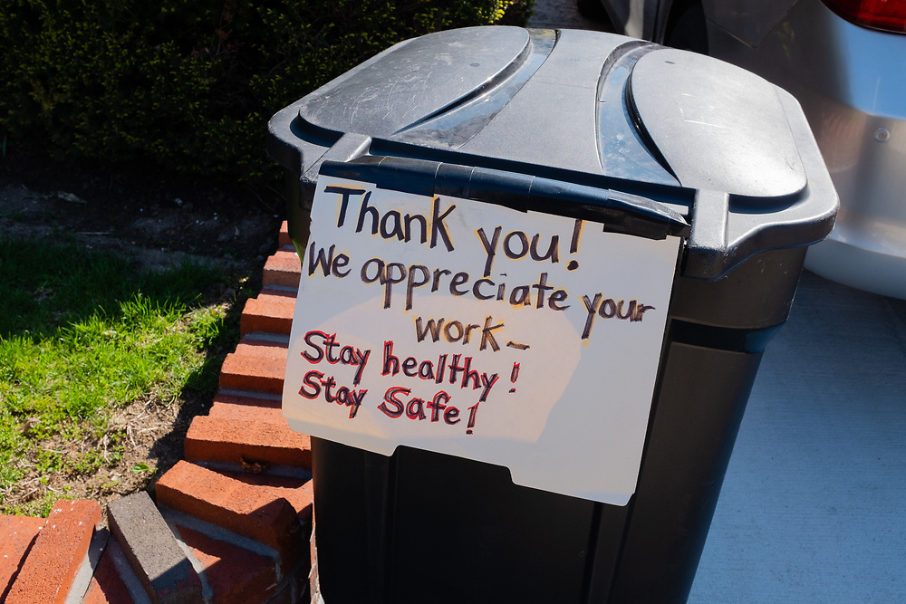 """Brooklyn, NY - 17 April 2020. A trash bin in front of a residence on E 29th St. in Brooklyn's Midwood neighborhood with a hand-lettered sign giving thanks to Department of Sanitation workers: """"Thank You! We appreciate your work! Stay Healthy! Stay safe!"""""""