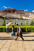 Tibetan pilgrims walk along Beijing Middle Road with the Potala Palace behind, Lhasa, Tibet (Xizang), China.