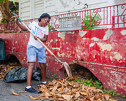Deja-Marie Simon clean up brush and debris from underneath a vacant residence.  Residents and volunteers gather for the Garden Street neighborhood cleanup and block Party hosted by E's Garden and Things, Long Path/Garden Street Community Association, and the Economic Development Authority's Enterprise and Commerical Zone Commission.  St. Thomas, USVI.  5 September 2015.  © Aisha-Zakiya Boyd